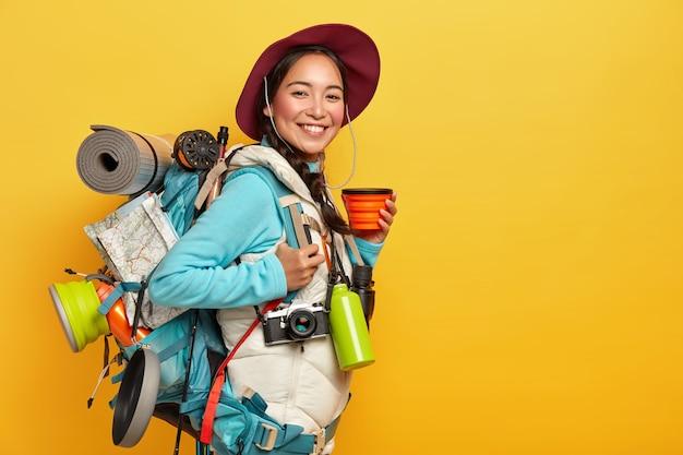 Turista femminile felice beve caffè o tè, posa con zaino, straccio arrotolato, indossa cappello, maglione e gilet, si ferma durante il viaggio, isolato su muro giallo Foto Gratuite