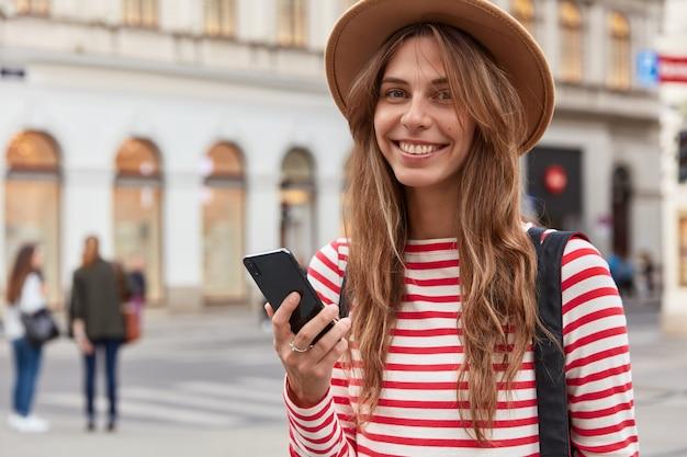 Turista femminile felice utilizza le informazioni dal blog di viaggio, tiene lo smartphone, cammina per le strade della città, indossa un cappello elegante e un maglione a righe Foto Gratuite