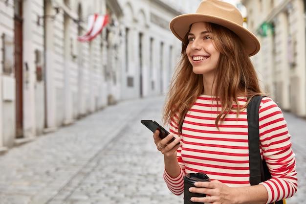 幸せな女性の旅行ブロガーは、ルートアプリケーションを使用し、最新のスマートフォンデバイスを保持し、古代都市を歩き、持ち帰り用のコーヒーを飲みます 無料写真