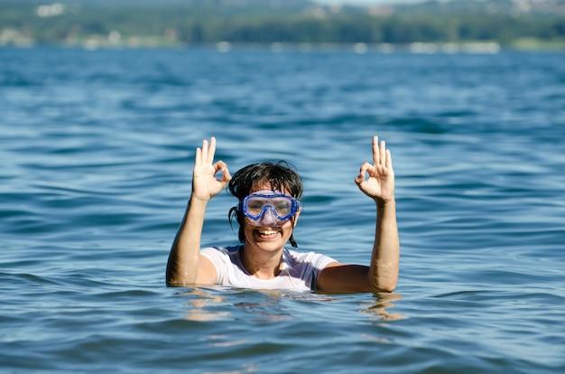 湖の穏やかな水の真ん中で短い髪の幸せな女性 無料写真