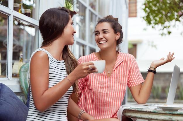 Счастливые самки отдыхают во время перерыва на кофе, обсуждают свой будущий проект, используют современный портативный компьютер. лучшие друзья встречаются в кофейне, радостно переглядываются, приятно беседуют. Бесплатные Фотографии