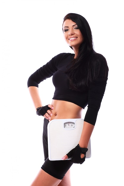 Happy fitness girl holding scales Free Photo