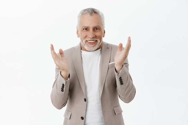 Happy flattered senior man in suit clap hands and looking excited Free Photo