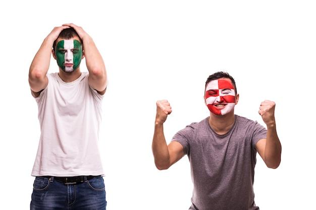 クロアチアの幸せなサッカーファンは、塗装された顔でナイジェリアの動揺したサッカーファンの勝利を祝います 無料写真