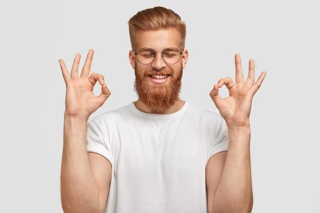 満足のいく表情で幸せなセクシーな若い男は、大丈夫なジェスチャーをし、幸せで目を閉じます 無料写真