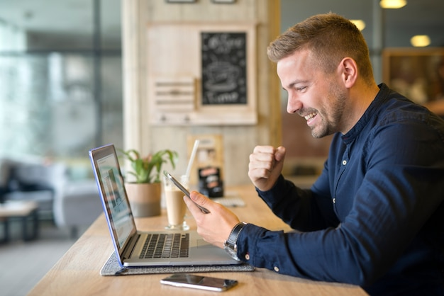 man cheering up in front of a mobile device