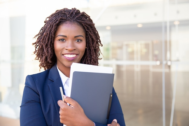 Happy friendly office assistant posing outside Free Photo