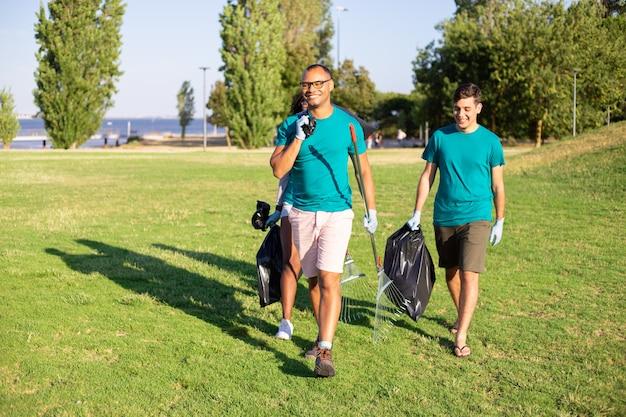 Happy friendly volunteers carrying litter Free Photo