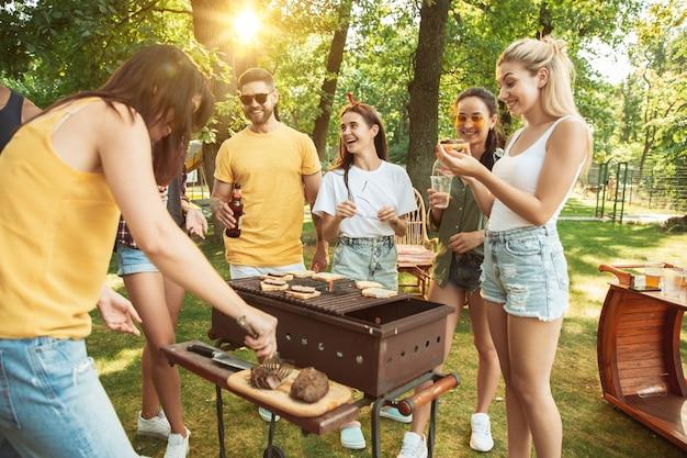 Счастливые друзья пьют пиво и барбекю в солнечный день Бесплатные Фотографии