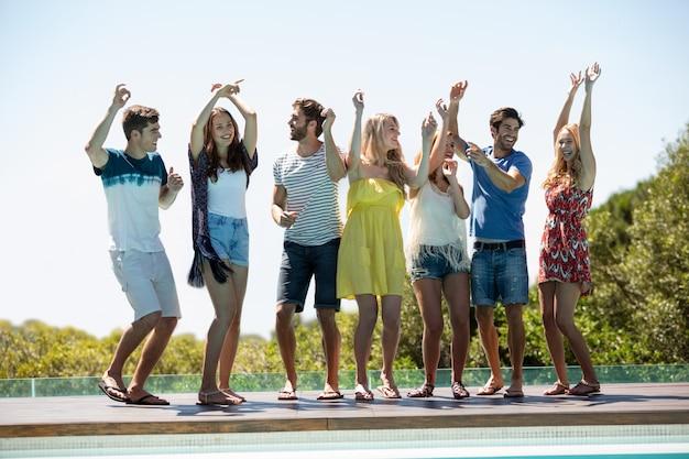 Happy friends dancing near the swimming pool Premium Photo