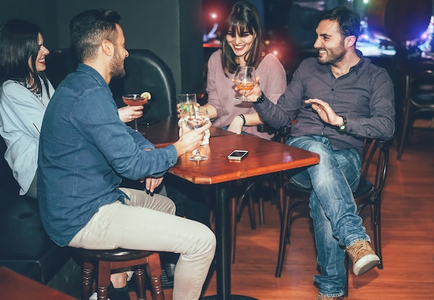 Happy friends drinking cocktails inside jazz cocktail bar Premium Photo