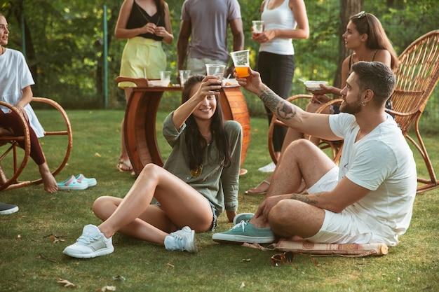 Счастливые друзья едят и пьют пиво на ужине-барбекю во время заката Бесплатные Фотографии