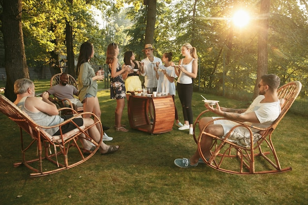 日没時間のバーベキューディナーでビールを食べたり飲んだりして幸せな友達 無料写真