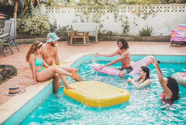 Happy friends floating with air lilo ball at swimming pool party - young people having fun on summer holidays vacation Premium Photo