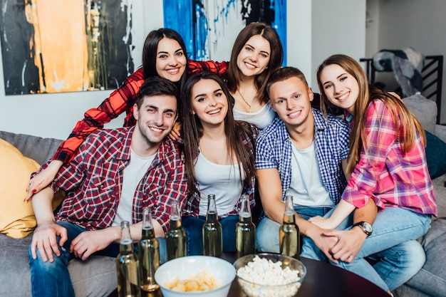 Happy friends or football fans watching soccer on tv and celebrating victory at home. eating popcorn and drink beer. Premium Photo