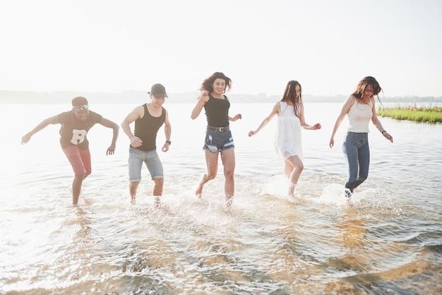Gli amici felici si divertono sulla spiaggia - giovani che giocano in acqua all'aperto durante le vacanze estive. Foto Gratuite