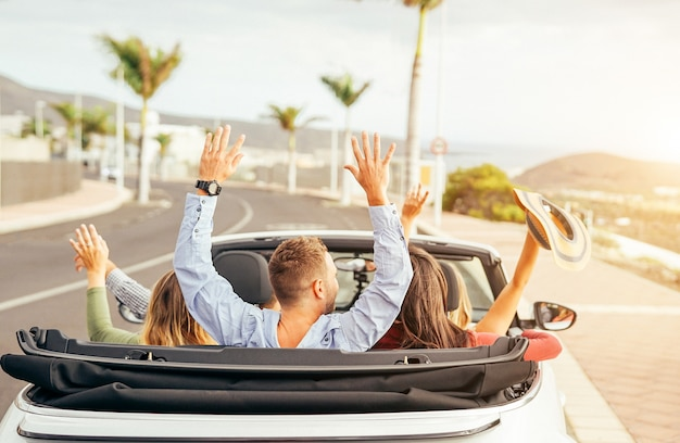Happy friends having fun in convertible car at sunset in vacation Premium Photo
