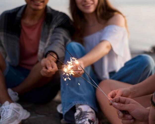 Счастливые друзья держат фейерверк крупным планом Бесплатные Фотографии