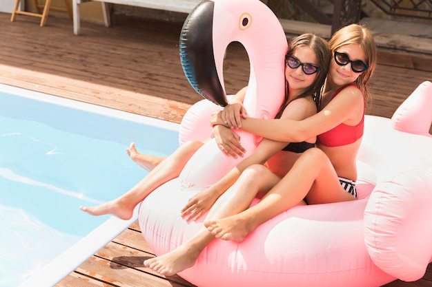 Happy friends hugging nearby pool Free Photo