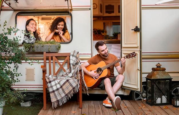 Счастливые друзья в фургоне играют на гитаре Бесплатные Фотографии
