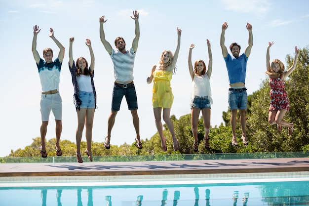 Happy friends jumping near swimming pool Premium Photo