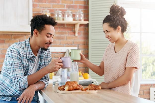 Amici felici si incontrano nell'atmosfera di casa, tintinnano tazze, mangiano deliziosi croissant, Foto Gratuite