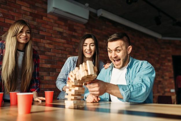 Счастливые друзья играют в дженгу за столом в кафе Premium Фотографии