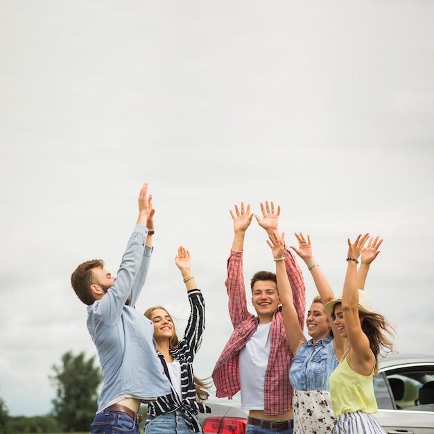 Счастливые друзья, подняв руки на открытом воздухе Premium Фотографии