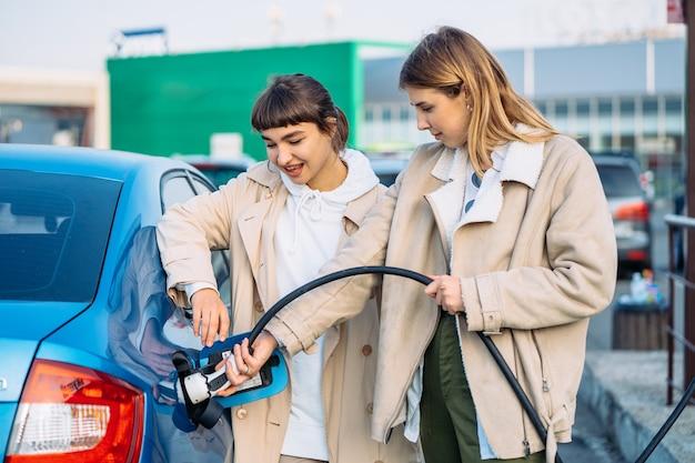 Gli amici felici fanno rifornimento di carburante alla stazione di servizio. Foto Gratuite