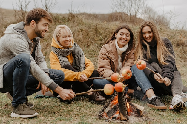 Happy friends roasting apples outdoors Free Photo