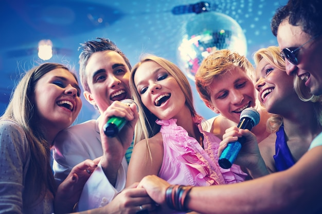 Happy friends singing karaoke together Free Photo