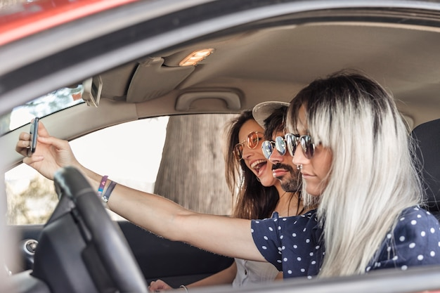 Happy friends sitting inside the car taking selfie through mobile phone Free Photo