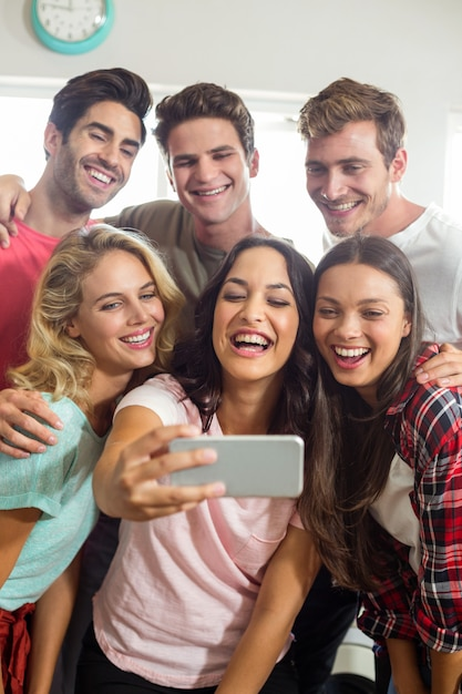 Happy friends smiling while taking selfie at home Premium Photo