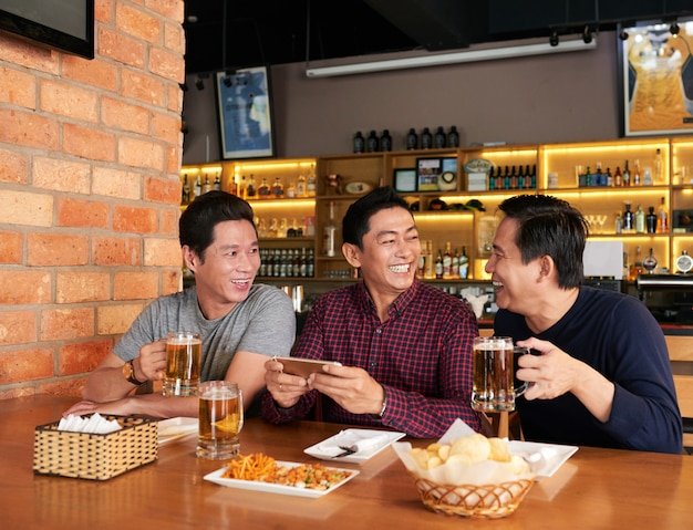 Happy friends spending time together in a beer pub Free Photo