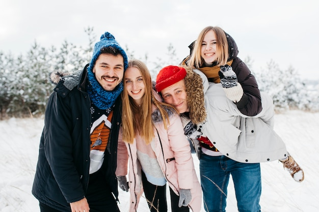 Happy friends standing in winter forest Free Photo