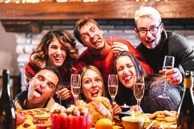 シャンパンでクリスマスの時期を祝うクレイジー酔って自分撮りを取っている幸せな友達 Premium写真