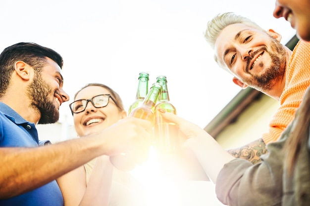 Happy friends toasting beers at sunset outdoor Premium Photo
