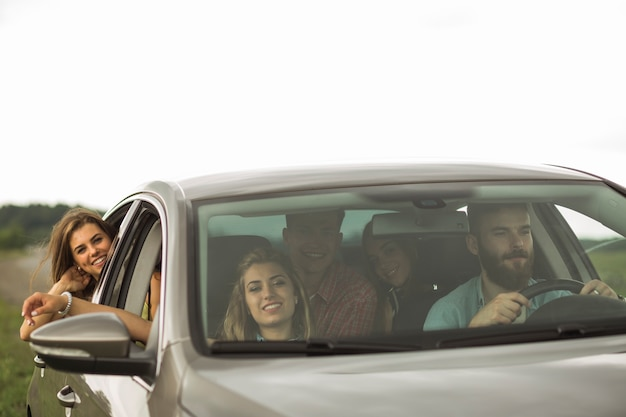 Happy friends travelling in luxury car Free Photo