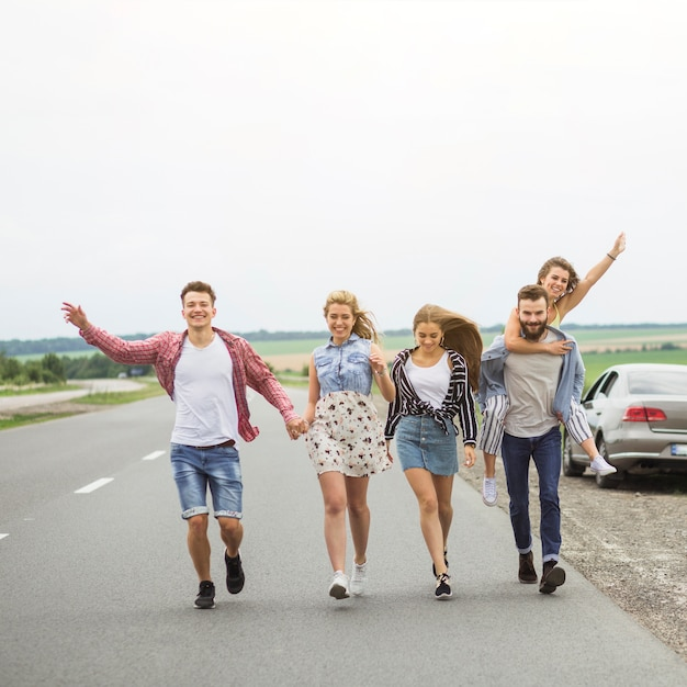 Happy friends walking on road together making fun Free Photo