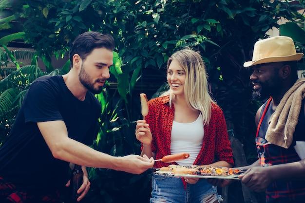 Счастливые друзья с барбекю на природе Premium Фотографии