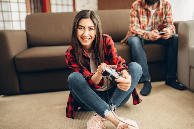 Счастливые друзья с джойстиками играют на приставке Premium Фотографии