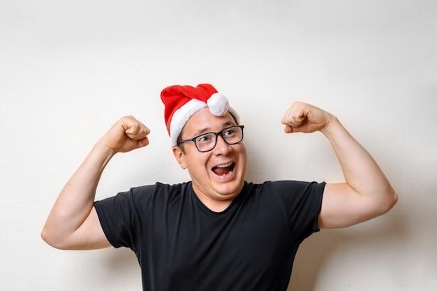 Счастливый смешной сильный молодой человек санта в красной шляпе. декабрьские каникулы. студия Premium Фотографии