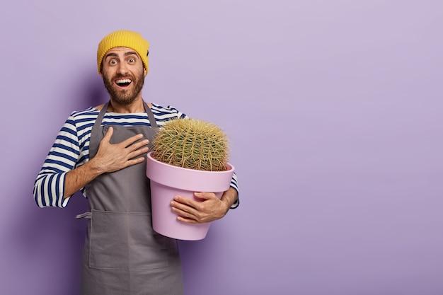 幸せな庭師は彼の庭のコレクションで新しい種類のサボテンを手に入れてくれた友人に感謝し、胸に手を置いています 無料写真