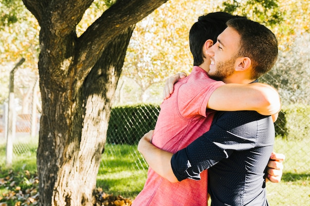 Happy gay couple embracing in park Free Photo
