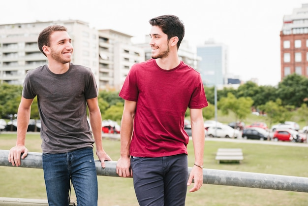 Happy gay couple standing by railing Free Photo