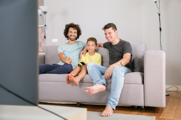 homosexuals' parents having a great time with their son in front of the TV