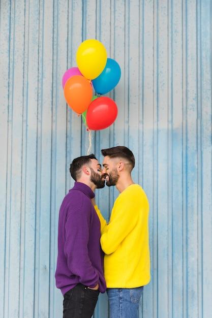 Happy gay sweethearts kissing and holding balloons Free Photo
