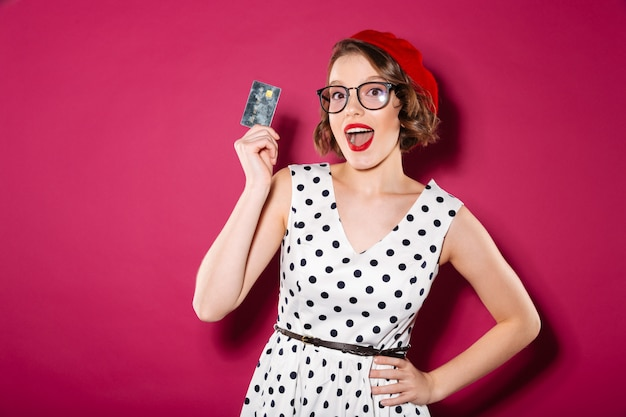 Happy ginger woman in dress and eyeglasses holding credit card while looking at the camera over pink Free Photo