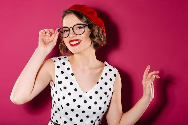 Happy ginger woman in dress and eyeglasses looking at the camera over pink Free Photo