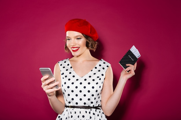 Happy ginger woman in dress holding passport with tickets and using smartphone over pink Free Photo